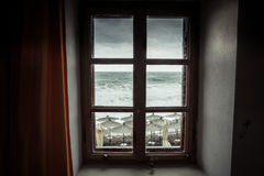 Vintage window with dramatic sea view with big stormy waves and dramatic overcast sky during rain and storm weather in fall season Royalty Free Stock Photos
