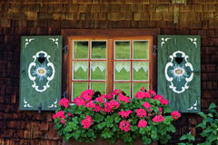 Vintage window with flower box. A traditional Bavarian window with shutters and floxer box in summer Stock Photo