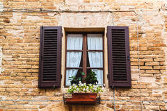Vintage window with flowers and shutters in Italy Royalty Free Stock Photo