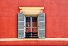 Vintage window with grey shutters in old red stucco house, Nice, France royalty free stock images