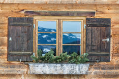 Vintage Window of old alpine house. Wooden rustic background. Reflections of snow spotted mountains in window glass Stock Photo