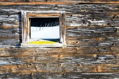 Vintage window of old wooden cabin mirrors winter landscape. Wooden rustic background. Royalty Free Stock Photography