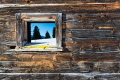 Vintage window of old wooden cabin mirrors winter mountain landscape. Wooden rustic background. Stock Image