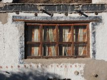Vintage window of a rural house: old wooden brown frames, through glass cloth curtains are visible, white clay wall. Vintage window of a rural house: old wooden Royalty Free Stock Photography