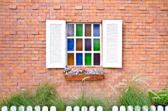 Vintage window with shutters that open and fresh flowers with colored glass and brick wall Stock Images