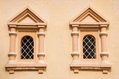Vintage windows. Beige-pink wall of the old church with windows Stock Images