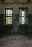 Vintage Windows and Curtains - Abandoned Hospital / Sanitarium - New York. An interior view of windows with tattered blue curtains inside an abandoned hospital stock image