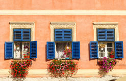 Vintage windows with open wooden shutters and fresh flowers Stock Photography