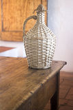 Vintage wine bottle basket in old house. Vintage wine bottle basket on table in old country house Royalty Free Stock Photos