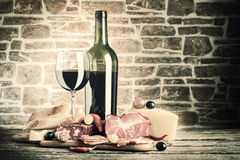 Vintage Wine, Cheese and Meat. Wine, cheese and meat on a wooden rustic table, vintage food background. Lomography style Stock Photos