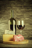 Vintage Wine, Cheese and Meat. Wine, cheese and meat on a wooden rustic table, vintage food background. Lomography style Royalty Free Stock Image
