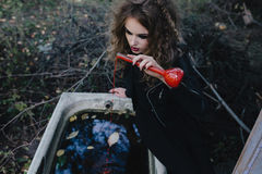 Vintage witch with elixir in hand Royalty Free Stock Image