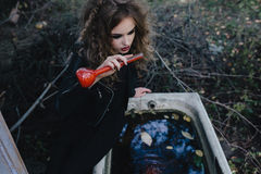 Vintage witch with elixir in hand. Vintage witch performs magical ritual, with elixir in hand on the eve of Halloween stock photography
