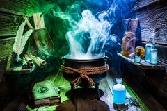 Vintage witcher cauldron with magic potions and books for Halloween stock photos