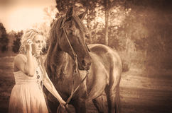 Vintage woman and black horse Royalty Free Stock Images