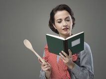 Vintage woman with cookbook. Smiling vintage woman holding an open cookbook and a wooden spoon Royalty Free Stock Photography