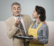 Vintage woman cooking muffins for her husband Stock Photography