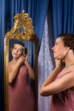 Vintage woman in mirror. Stunning vintage 1920s woman looking in an antique mirror stock photo
