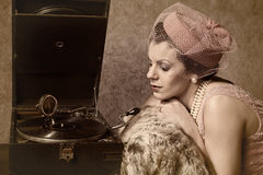 Vintage woman and old music. Vintage 1920s style lady in pink listening to an antique record player royalty free stock images