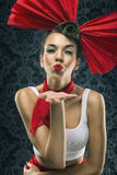 Vintage woman in red dress with big red bow in head Stock Photography