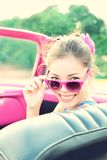 Vintage woman in retro car. Vintage woman in pink retro car. Retro vintage processed photo of girl on road trip driving in vintage cabriolet car during summer Royalty Free Stock Photos