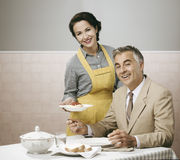 Vintage woman serving lunch to her husband Stock Images