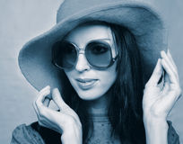 Vintage woman in sunglasses and  hat. Portrait of young woman in sunglasses and red hat in retro style in cold tones Stock Image