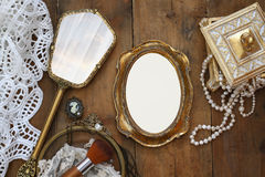 Vintage woman toilet fashion objects next to blank photo frame. Top view image of vintage woman toilet fashion objects next to blank photo frame on old wooden Royalty Free Stock Images