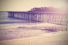 Vintage wood bridge at beach sunset, California, USA. Royalty Free Stock Photography