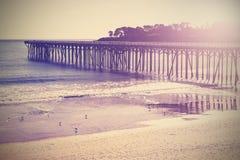 Vintage wood bridge at beach sunset, California, USA. Royalty Free Stock Photography