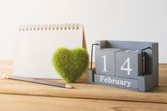 Vintage wood calendar for February 14 with green heart, notebook. Pencil on wood table love and valentine's day concept background, backdrop Stock Photo