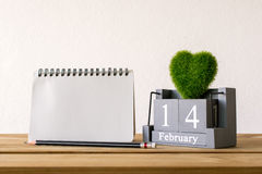 Vintage wood calendar for February 14 with green heart, notebook. Pencil on wood table love and valentine's day concept background, backdrop Royalty Free Stock Image