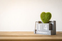 Vintage wood calendar for February 14 with green heart on wood t. Able love and valentine's day concept background, backdrop Royalty Free Stock Images
