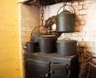 Vintage wood cooking stove with pots. An old fashioned wood fired cooking stove and oven with large black metal pots Stock Photos
