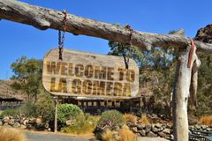 Old vintage wood signboard with text welcome to La Gomera hanging on a branch. Vintage wood signboard with text welcome to La Gomera hanging on a branch royalty free stock photos