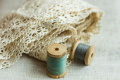 Vintage wood spools with green and grey threads on linen fabric, cotton lace, sewing hobby concept Royalty Free Stock Image
