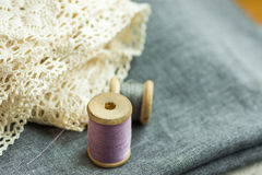 Vintage wood spools with lilac and grey threads on folded wool fabric, cotton lace, sewing hobby concept Royalty Free Stock Image