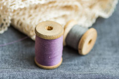 Vintage wood spools with lilac and grey threads on folded wool fabric, cotton off-white lace, hobby swing concept. Copyspace, header for website Stock Photo