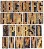 Vintage wood type alphabet. Complete English alphabet - a collage of 26 isolated vintage wood letterpress printing blocks, scratched and stained by ink Royalty Free Stock Photos