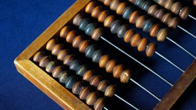 Vintage wooden abacus close up. Counting wooden knuckles. Part of the old end of the abacus on a dark blue background.