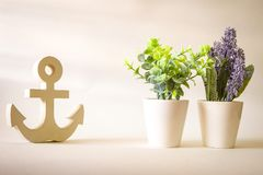 Vintage wooden anchor with purple lavender and tree in pot background. Vintage wooden anchor with purple lavender and tree in pot stock images