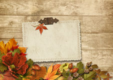 Vintage wooden background with card&autumn decorations Royalty Free Stock Images