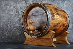 Vintage wooden barrel with tap in dark cellar. On gray concrete background royalty free stock photography