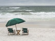 Vintage Wooden Beach Chairs on Stormy Beach stock images
