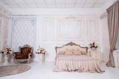 Vintage wooden bed with pink blanket. White vintage interior with a wooden bed and Versailles wallpaper. Vintage wooden bed with pink blanket Royalty Free Stock Photos