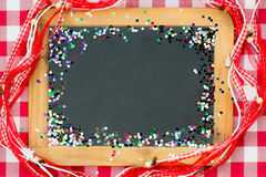 Vintage wooden blackboard with confetti Stock Image