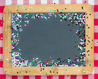 Vintage wooden blackboard with confetti Royalty Free Stock Photo