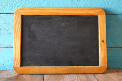 Vintage wooden blackboard on wooden table with space for text Stock Photography