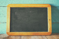Vintage wooden blackboard on wooden table with space for text Stock Image