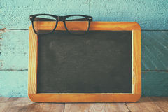 Vintage wooden blackboard on wooden table with space for text Royalty Free Stock Photography